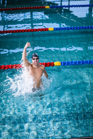 triumphing: Fit man triumphing with fist up in the pool