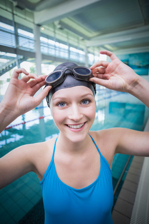 swimming goggles: Pretty woman putting on swimming goggles at the pool Stock Photo