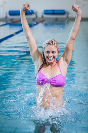 triumphing: Pretty woman triumphing with raised arms in the pool Stock Photo