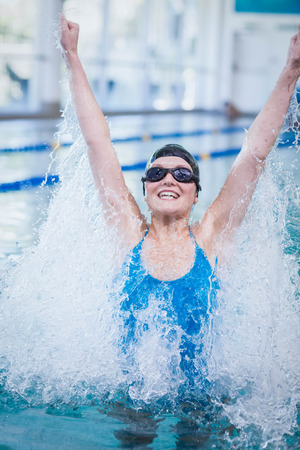 triumphing: Fit woman triumphing with raised arms at the pool
