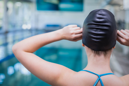 swim cap: Rear view of fit woman putting on swim cap at the pool Stock Photo