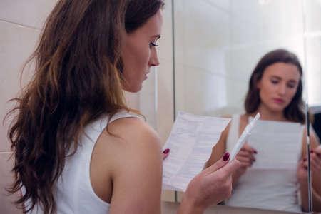 test de grossesse: Belle brune lire les instructions de test de grossesse tout en maintenant un test de grossesse dans la salle de bain à la maison