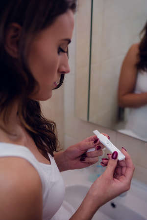 home pregnancy test: Beautiful brunette holding a pregnancy test in the bathroom at home