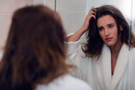 messy hair: Beautiful brunette with messy hair and bathrobe in the bathroom LANG_EVOIMAGES