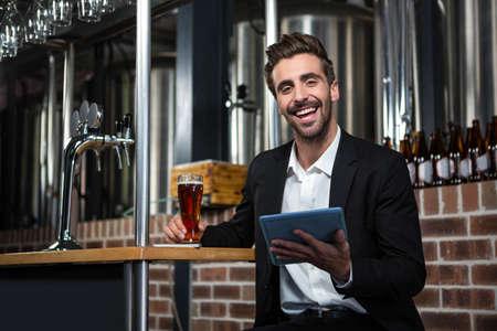 beer pump: Handsome businessman using tablet computer in a pub LANG_EVOIMAGES