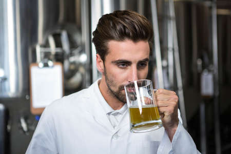microbrewery: Focused brewer testing his beer at the microbrewery