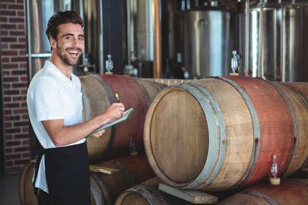 winemaker: Winemaker taking notes on clipboard on winefarm LANG_EVOIMAGES