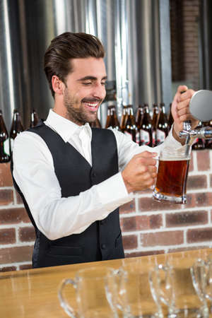 beer pump: Handsome barman pouring a pint of beer in a pub