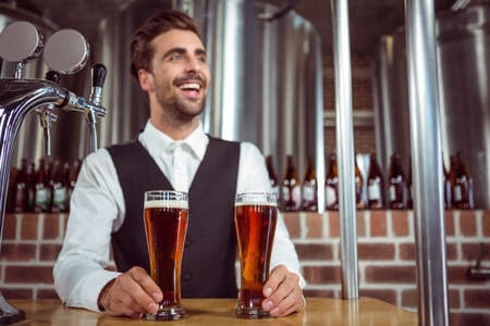 beers: Handsome barman giving two beers in a pub