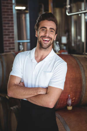 brewer: Handsome brewer crossing his arms in a brewery LANG_EVOIMAGES
