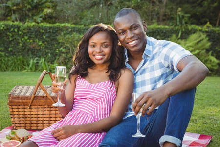 ethnic couple: Ethnic couple having a glass of champagne in the garden