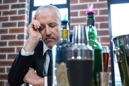 tired businessman: Tired businessman leaning on counter in a pub LANG_EVOIMAGES