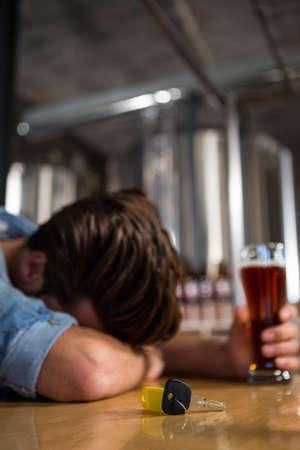 slumped: Drunk man sleeping at the bar holding his pint LANG_EVOIMAGES