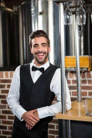 beer pump: Handsome barman smiling at camera in a pub