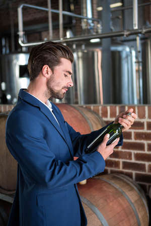 well dressed: Well dressed man examining bottle of wine at winefarm LANG_EVOIMAGES
