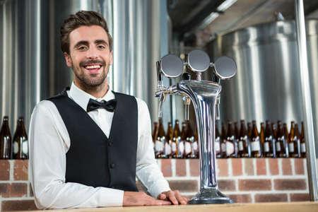 barman: Handsome barman smiling at camera in a pub