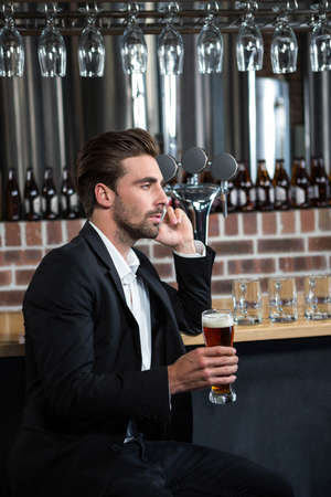 pint: Handsome businessman holding a pint in a pub LANG_EVOIMAGES