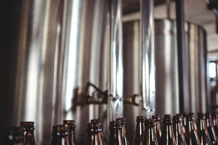 vats: Large vats of beer with bottles at the brewery