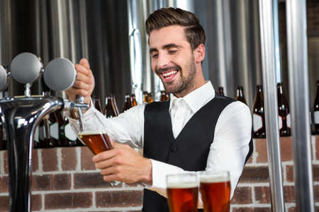 barman: Handsome barman pouring a pint of beer in a pub
