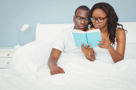 ethnic couple: Ethnic couple reading a book in the bed