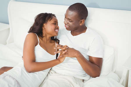 ethnic couple: Ethnic couple holding hands in bed