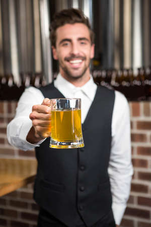 pint: Barman holding a pint in a pub