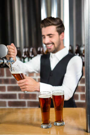 barman: Barman pouring a beer in a pub