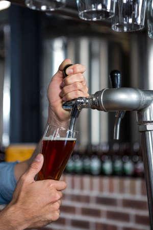 barman: Barman pouring pint of beer at the bar