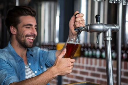 barman: Barman pouring beer in a pub