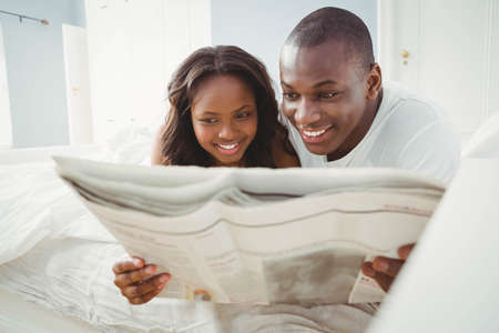ethnic couple: Ethnic couple reading the news in the bedroom LANG_EVOIMAGES