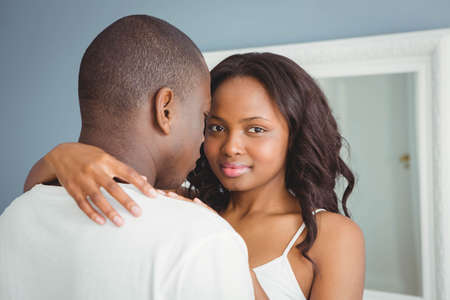 ethnic couple: Ethnic couple hugging in their room
