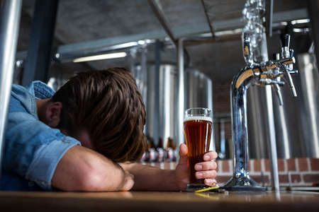 inebriated: Drunk man sleeping at the bar holding his pint LANG_EVOIMAGES