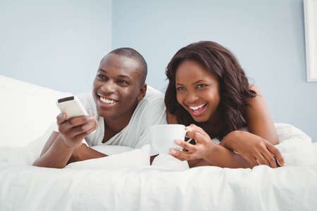 pareja viendo television: Ethnic couple watching tv in bed LANG_EVOIMAGES