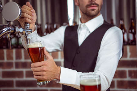 pint: Handsome barman pouring a pint of beer in a pub