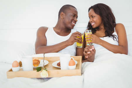ethnic couple: Ethnic couple having breakfast in their bed