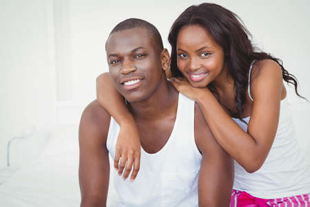 ethnic couple: Ethnic couple smiling at camera in their bedroom LANG_EVOIMAGES