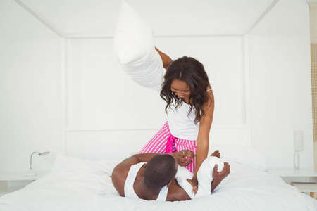 ethnic couple: Ethnic couple pillow fighting in the bedroom