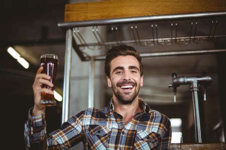 microbrewery: Happy brewer showing pint of beer at the local brewery LANG_EVOIMAGES