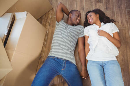 unwrapping: Ethnic couple lying on the floor of their new house
