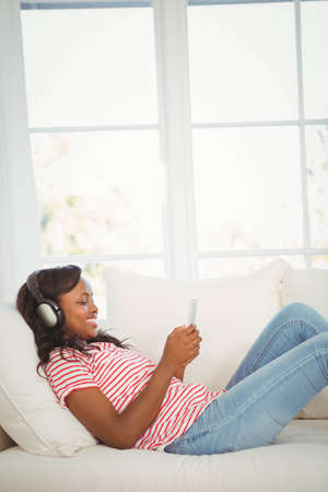 woman couch: Woman listening to music with headphones lying on the couch