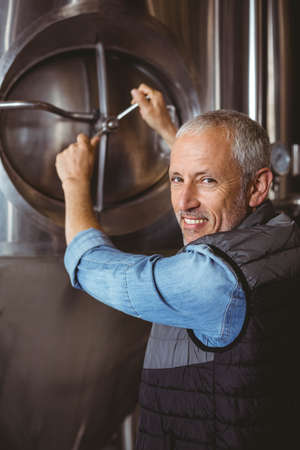 brewer: Happy brewer checking large vats at the local brewery LANG_EVOIMAGES