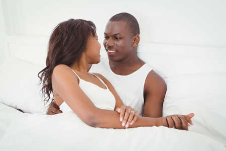 ethnic couple: Ethnic couple about to kiss sitting on their bed