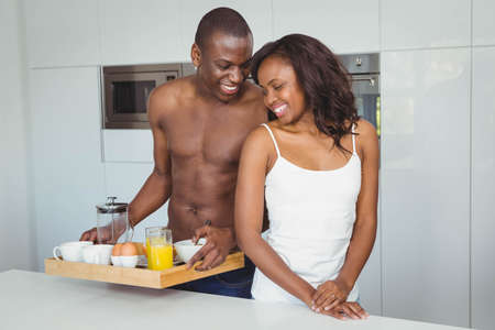 ethnic couple: Ethnic couple preparing breakfast on a tray in the kitchen
