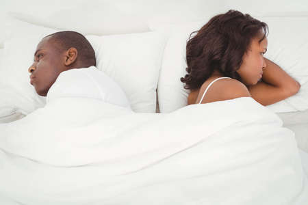 sulking: Ethnic couple sulking each other in their bed
