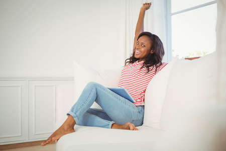 triumphing: Woman triumphing with raised arm on the couch LANG_EVOIMAGES