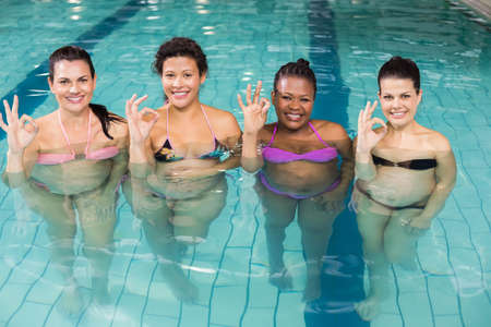 regnant: Smiling regnant woman doing OK sign at the swimming pool