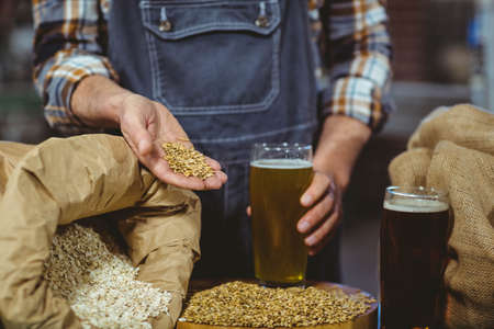 microbrewery: Happy brewer showing grain and produce at the local brewery LANG_EVOIMAGES