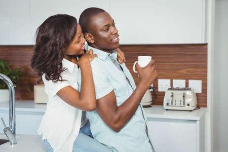 ethnic couple: Ethnic couple holding mugs in the kitchen