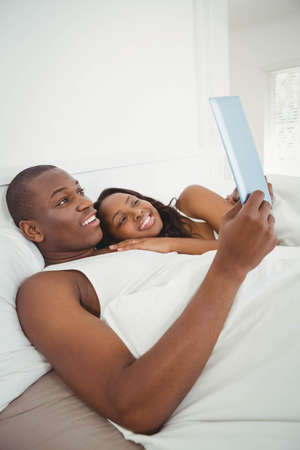 ethnic couple: Ethnic couple using tablet in the bed