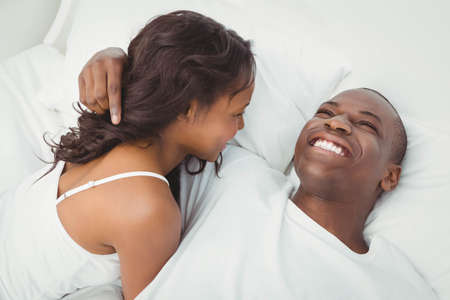 ethnic couple: Ethnic couple cuddling on their bed